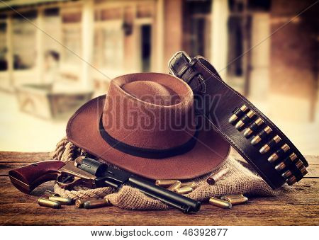 Western accessories on wooden table - Gun, hat and bullets poster