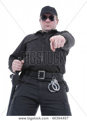 Policeman wearing black uniform and glasses pointing in ordering manner