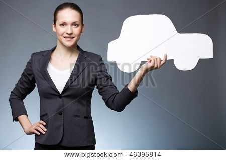 Portrait of young dealer holding paper car and looking at camera