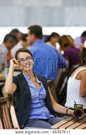 Pretty Young Woman Sitting in a Restaurant gardens