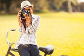 smiling young woman using a camera to take photo outdoors at the park poster