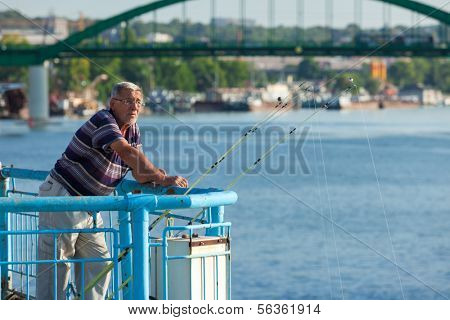 BELGRADE, SERBIA - AUG 15: Senior citizen fishing from the dock on August 15, 2012 in Belgrade, Serbia. Danube river is very popular fishing location.