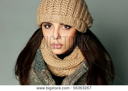 Closeup portrait of a young thoughtful woman in warm winter outfit on gray background