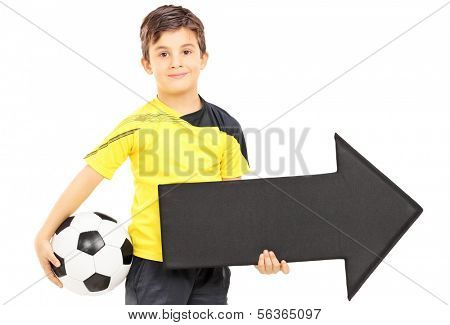 Smiling boy in sportswear holding a soccer ball and black arrow pointing right isolated on white background