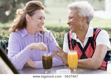 Two Female Friends Enjoying A Beverage By A Golf Course