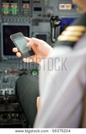 Pilots using smartphone in cockpit of private jet