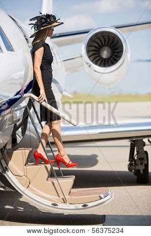 Full length side view of wealthy woman disembarking private jet at airport terminal