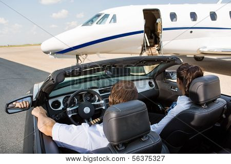 Rear view of pilot and stewardess in convertible parked against private jet at terminal
