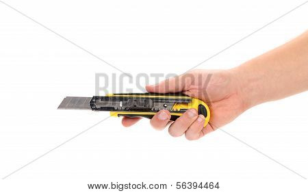 Hand holds yellow stationery knife