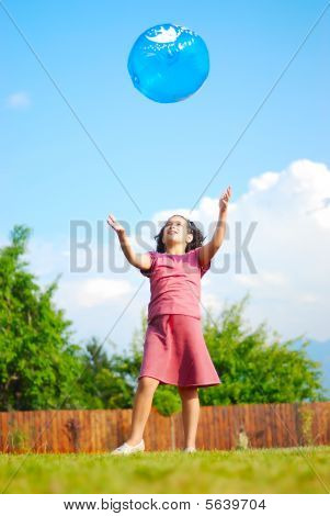 Little cute girl playing with a ball on green garden