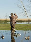 A hunter calling ducks on his duck call poster