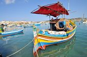 Traditional Maltese fishing boats called Luzzu in the harbour of Marsaxlokk Malta. poster