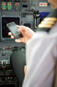 Pilots using smartphone in cockpit of private jet poster