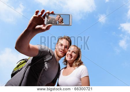 happy couple selfie by smart phone with sky background caucasian poster