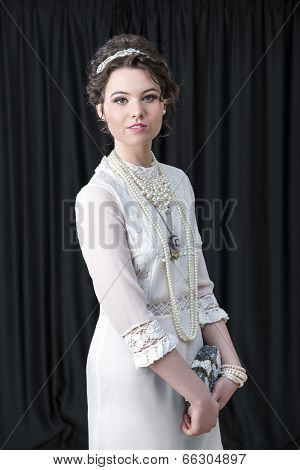 Portrait of beautiful Caucasian female model wearing Victorian style white dress and jewellery against black backdrop