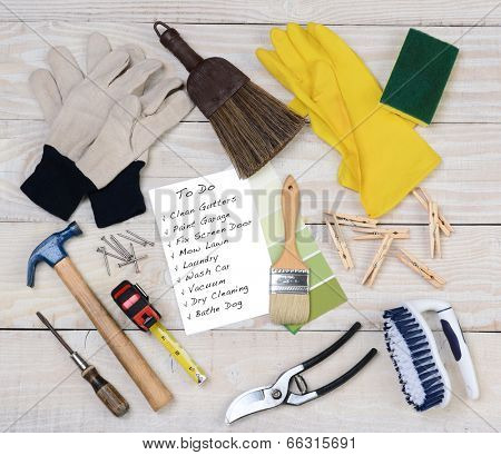 A Honey-Do List surrounded by the tools necessary to do the jobs. Items include: hammer, nails, paint brush, gloves, rubber gloves, scrub brush, paint chips, clothes pins, pruning shear. Square format