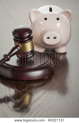 Gavel and Piggy Bank on Reflective Wooden Table.