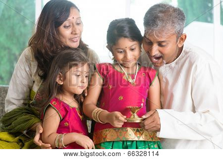 Indian family in traditional sari celebrate diwali or deepavali at home, little girl hands holding oil lamp with father indoors. poster