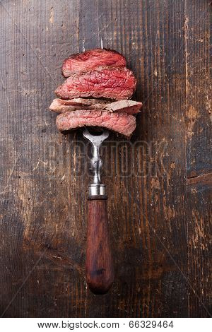 Slices Of Beef Steak On Meat Fork On Wooden Background