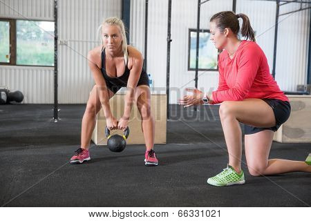 Woman lifts kettlebell with personal trainer
