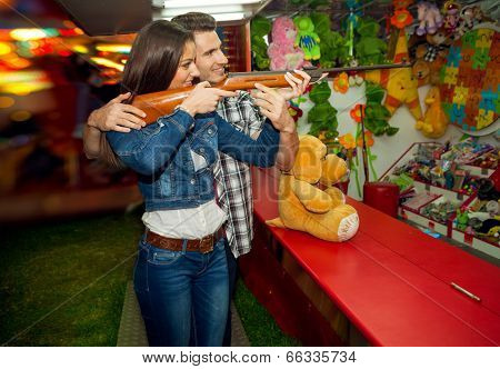 Young couple playing shooting games while visiting an amusement park arcade at night time, having fun with color lights and rides in the background, man helping woman.