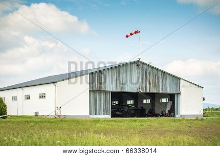 Aircraft garage top anemometer behind blue sky