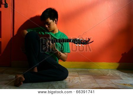 Young asian teen playing the guitar in a living room