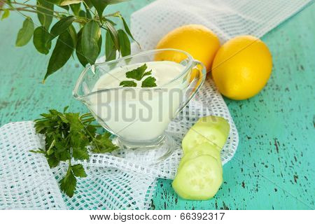 Cucumber yogurt in glass bowl, on color napkin, on wooden background poster