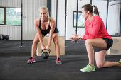 Young woman lift kettlebells with help of a instructor at fitness gym center. poster