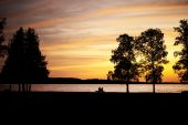Elderly couple silhouetted sitting on a bench by lake at sunset poster