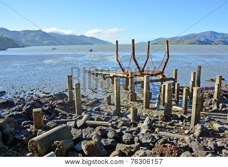 Governors Bay derelict ships' graveyard and cradle on the rocky shore at low tide. poster