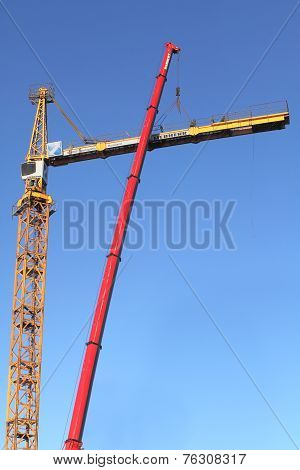 Yellow Construction Crane During Assembly Using A Mobile Crane.