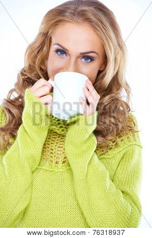 Blue eyed woman in a stylish green polo neck jersey enjoying a mug of hot coffee smiling at the camera