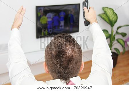 Young man sitting on the couch watching a football game on tv