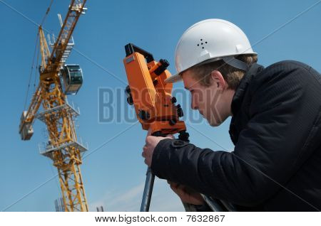 worker surveyor measuring distances elevations and directions on construction site by theodolite level transit equipment poster