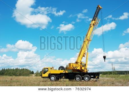 yellow automobile crane with risen telescopic boom outdoors over blue sky poster