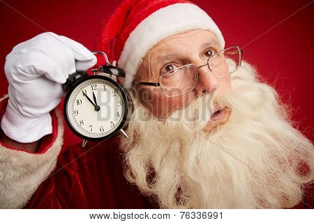 Perplexed Santa holding clock showing five minutes to xmas by his ear