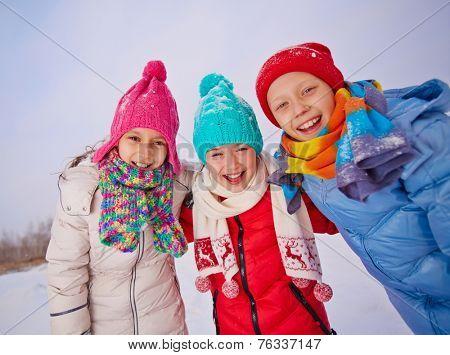 Group of ecstatic children in winterwear having fun outside