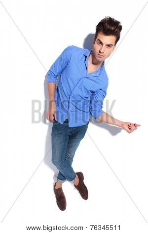 Full body image of a young fashion man looking at the camera while snapping his fingers.