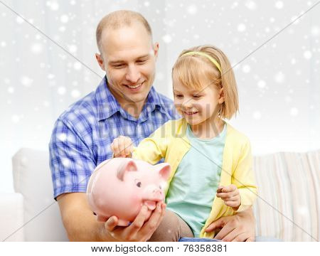family, children, money, investments and happy people concept - happy father and daughter with big pink piggy bank