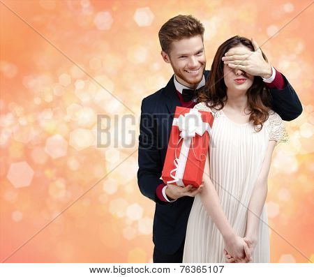 Giving a christmas present man covers eyes of his pretty girlfriend, gold light background