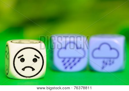 Concept Of Sad Storm Weather - Emoticon And Weather Dice On Green Backround