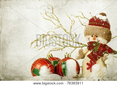 Vintage Christmas card with snowman and Christmas decoration in the snow