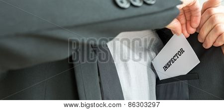 Inspector Removing A White Card With Inspector Sign From The Inner Pocket Of His Jacket