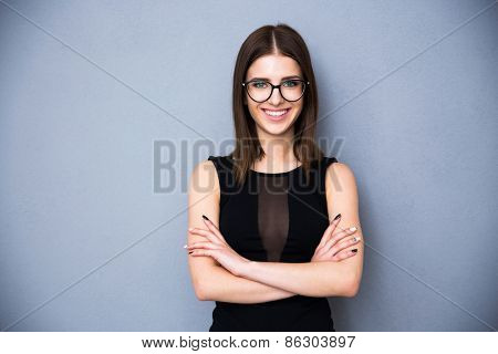 Portrait of a smiling woman in glasses and arms folded over gray background. Wearing in sexy black dress. Looking at the camera