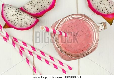 Dragon fruit smoothie in jar on white wood