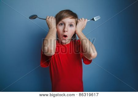 boy teenager European appearance in a red shirt put fork and spo