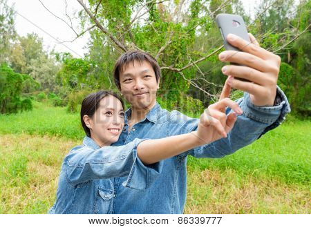 Couple fun taking self-portrait picture photos with mobile smart phone