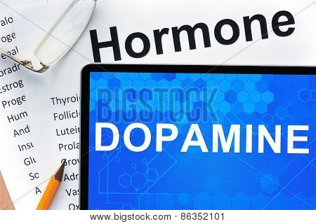 Papers with hormones list and tablet  with word dopamine.
