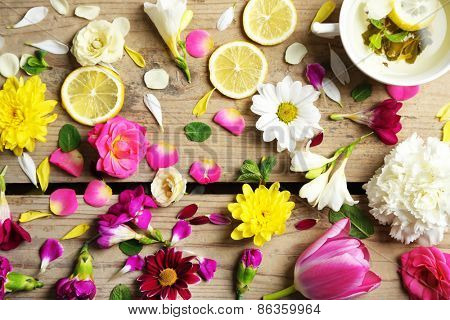 Cup of herbal tea with beautiful flowers, on wooden background poster